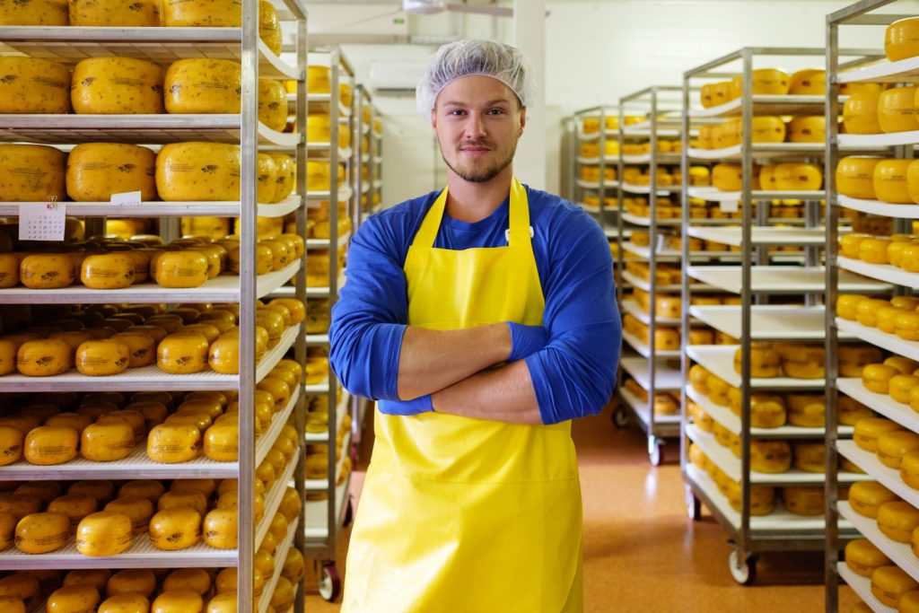 handsome cheesemaker is checking cheeses in his wo PXMR7JD 1
